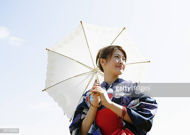 Woman dressed Yukata holding sunshade