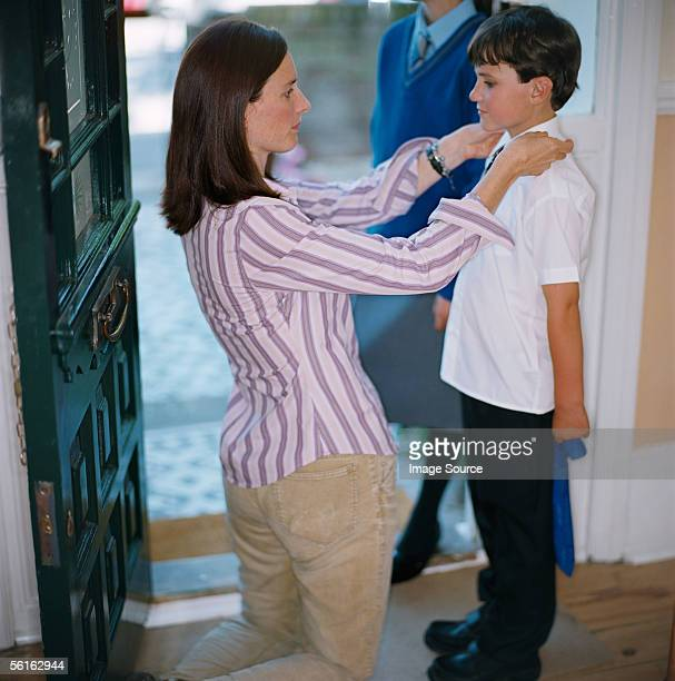 Woman dressing her son for school