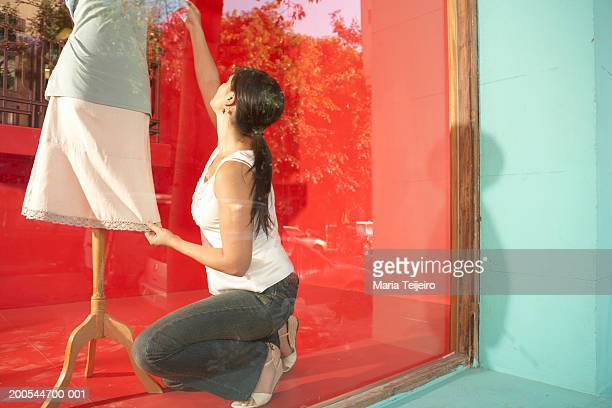 Woman dressing mannequin in shop window, view through glass, rear view