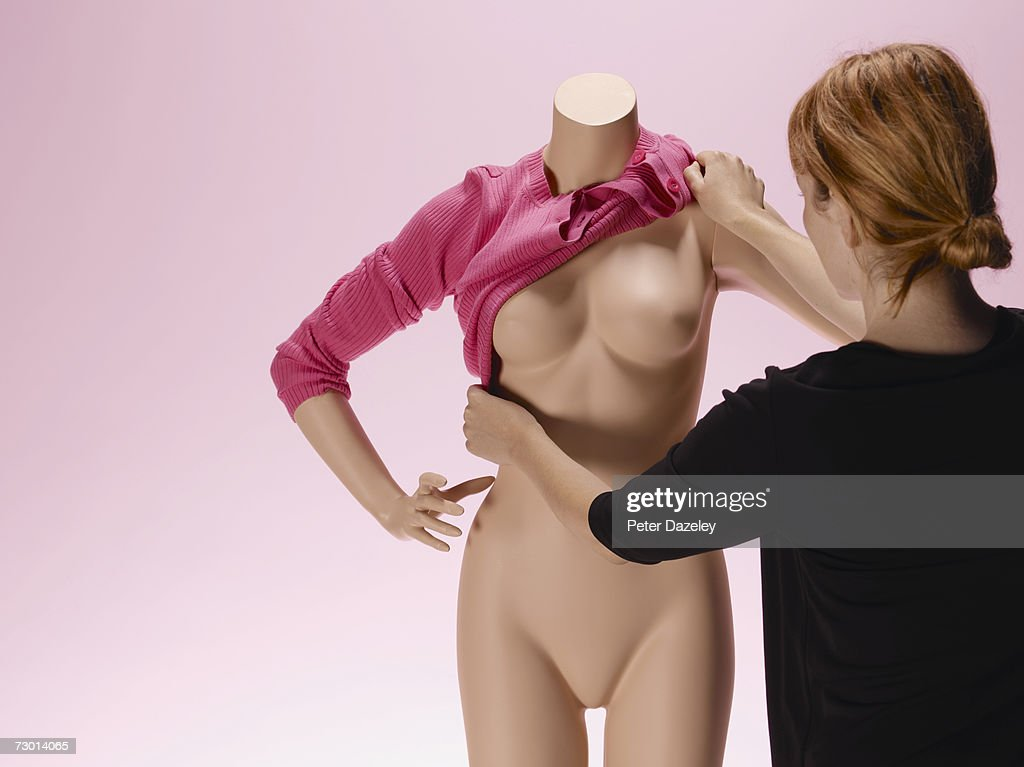 Woman dressing mannequin, rear view : Stock Photo