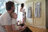 Woman dressing with husband and baby girl (6-9 months) in bedroom