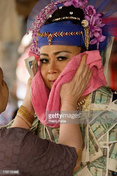 A woman dries the face of Phyu Lay a medium dancing in a shrine dedicated to the nats during the Taungbyon festival Every year in August hundreds of...