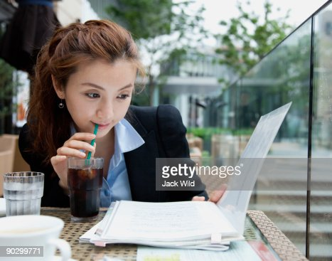 Woman driking, looking at documents : Stock Photo