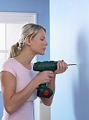 Woman Drilling a Hole in a Blue Wall