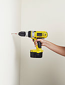 Woman drilling a hole in the wall
