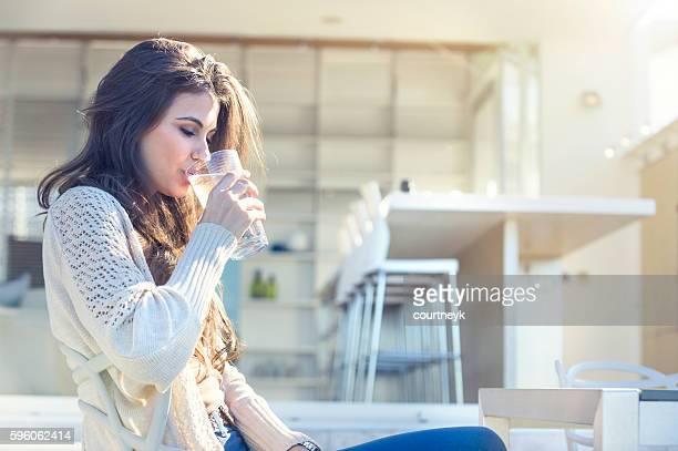 Femme buvant un verre d'eau.