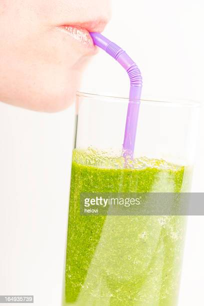 Woman drinking a green smoothie from a straw