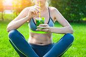 Woman drinking herbal tisane after fitness running workout on summer day. Fitness and healthy lifestyle concept