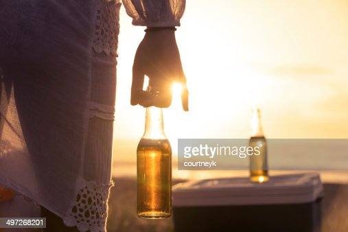 Woman drinking beer on the beach