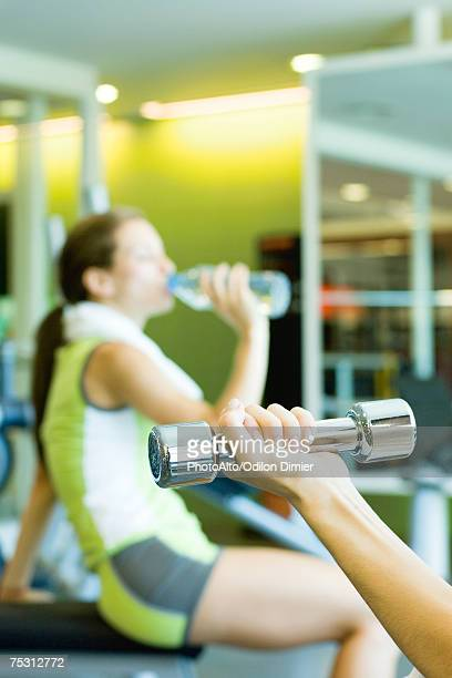 Woman drinking bottle of water, focus on second woman's arm holding dumbbell in foreground