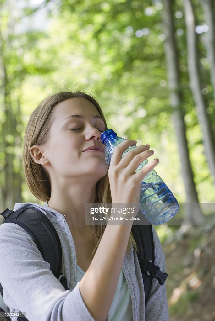 woman drinking bottled water in woods stock photo getty