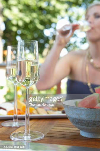 Woman drinking champagne at outdoor table (focus on champagne flute)
