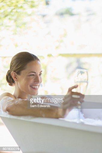 Woman drinking champagne in bathtub