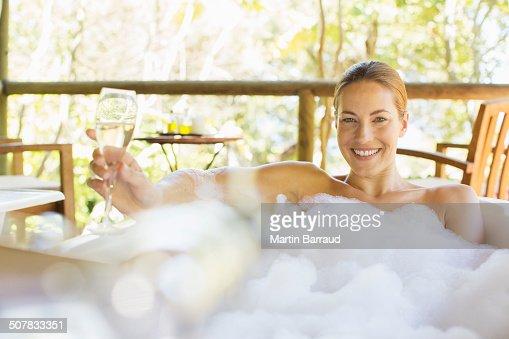 Woman drinking champagne in bubble bath