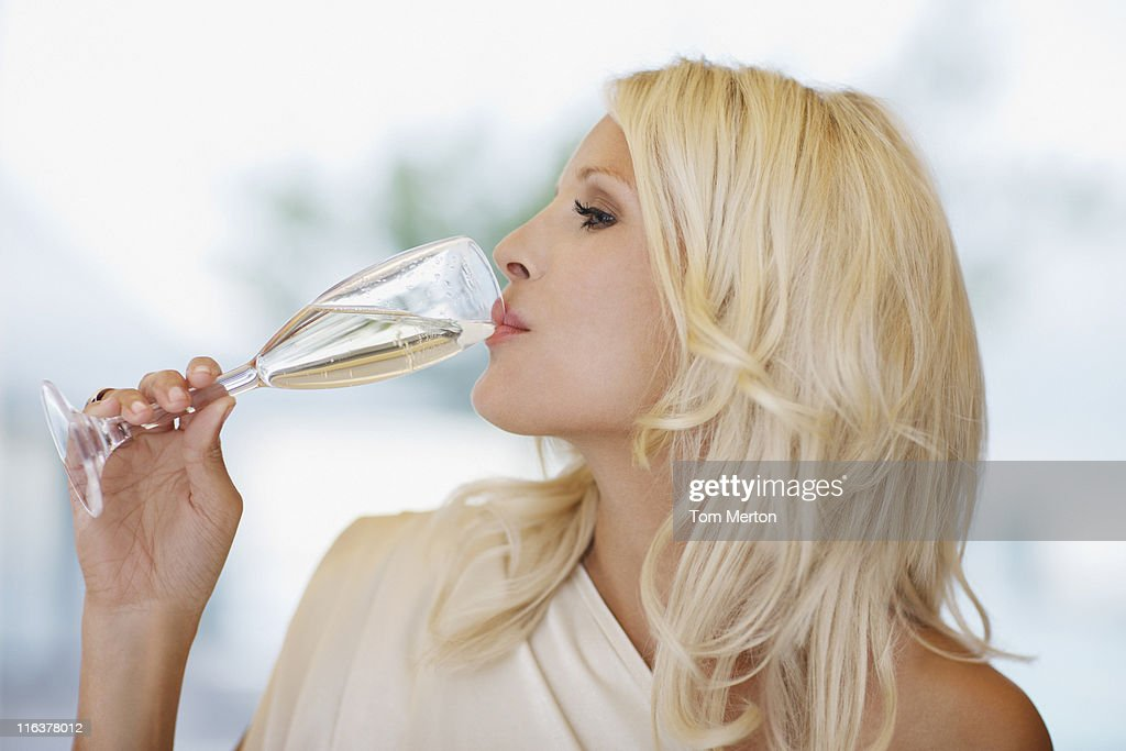 Woman drinking champagne : Stock Photo