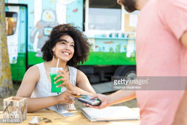 Woman drinking cocktail and using credit card