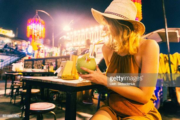 Woman drinking cocktail at night