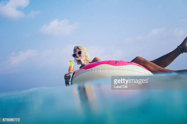 Woman drinking cocktail in the ocean, Maldives