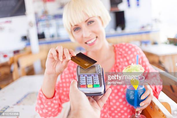 Woman drinking cocktail on beach and paying with credit card