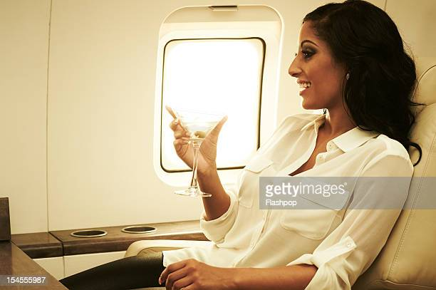 Woman drinking cocktail on private jet