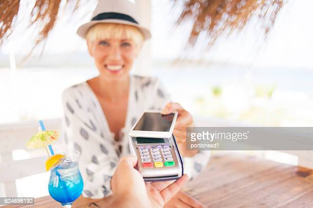 Woman drinking cocktails and using smart phone for contactless payment