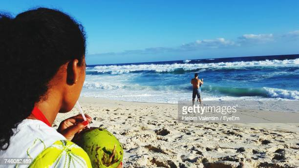 Woman Drinking Coconut Water At Beach Against Blue Sky