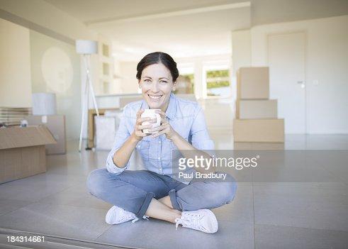 Woman drinking coffee among cardboard boxes