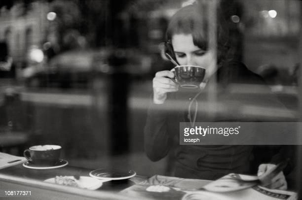 Femme buvant du café et de lecture de magazine Derrière la fenêtre