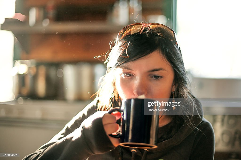 Woman drinking coffee at a hut.