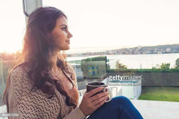 Woman drinking coffee at sunrise.
