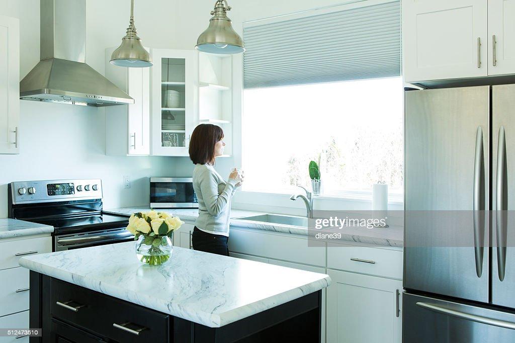 Femme buvant un café dans une cuisine moderne : Photo
