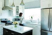 A woman stands looking out a window in a modern kitchen. She is drinking coffee.
