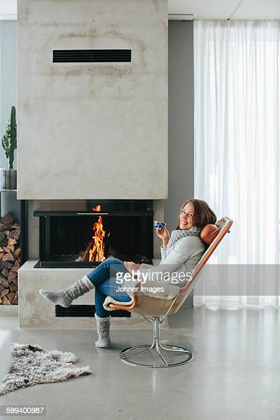 Woman drinking coffee in front of fireplace