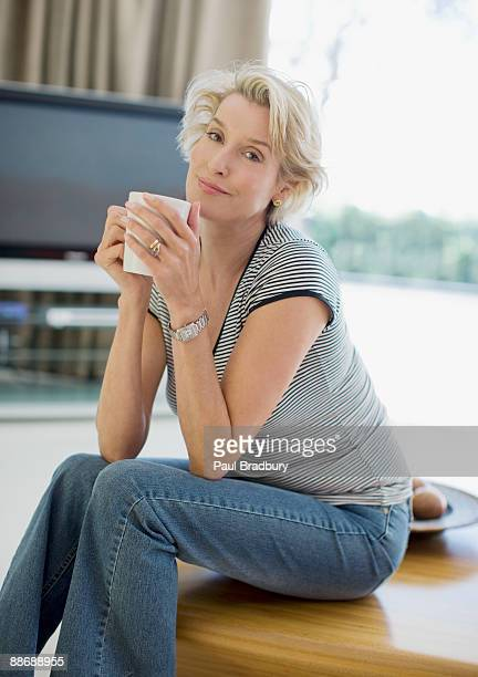 Woman drinking coffee in living room