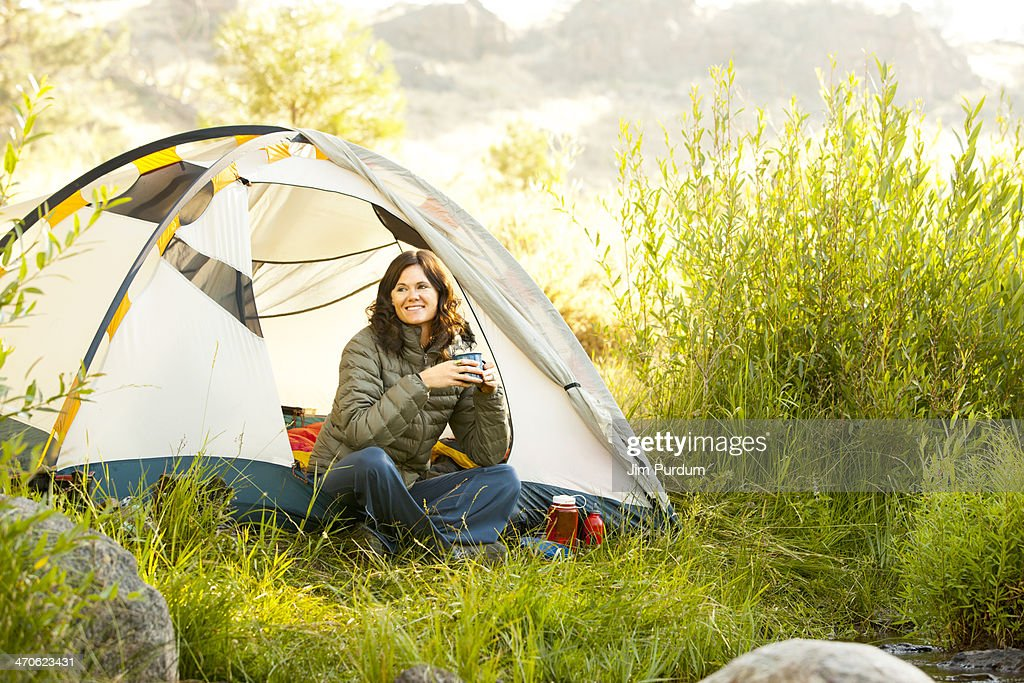Woman drinking coffee in tent at campsite : Stock Photo