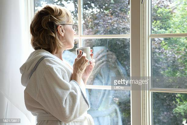 Femme regardant par la fenêtre, buvant un café chaud