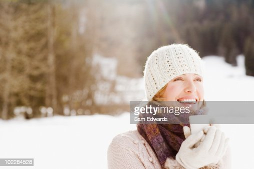 Woman drinking coffee outdoors in snow : Stock Photo