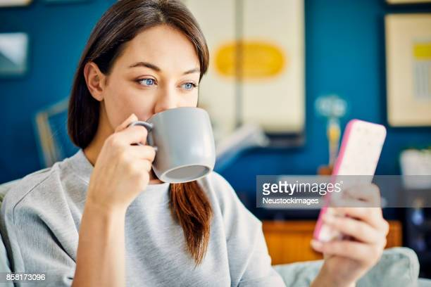 Woman drinking coffee while looking at smart phone