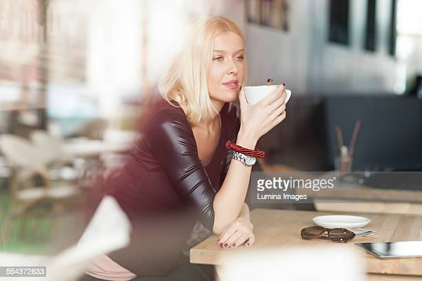 Woman drinking cup of coffee in cafe