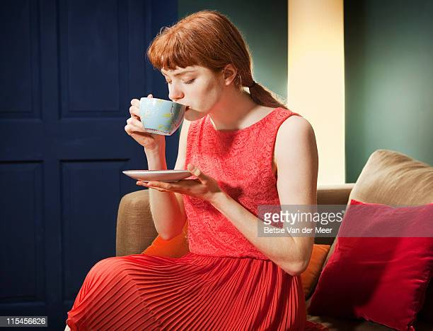 Woman drinking cup of tea sitting on sofa.