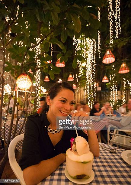 Woman drinking exotic drink in outdoor restaurant