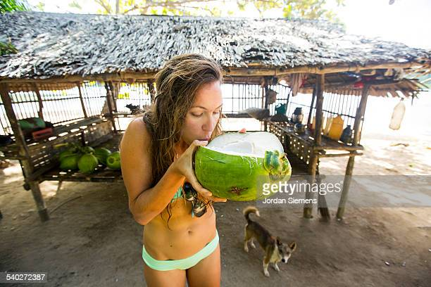 A woman drinking from a young fresh coconut.