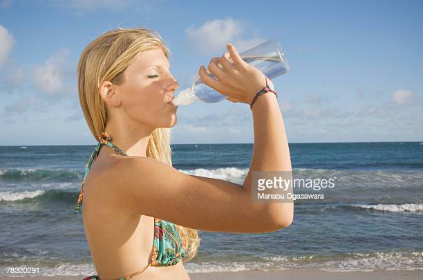 Woman drinking from water bottle on beach
