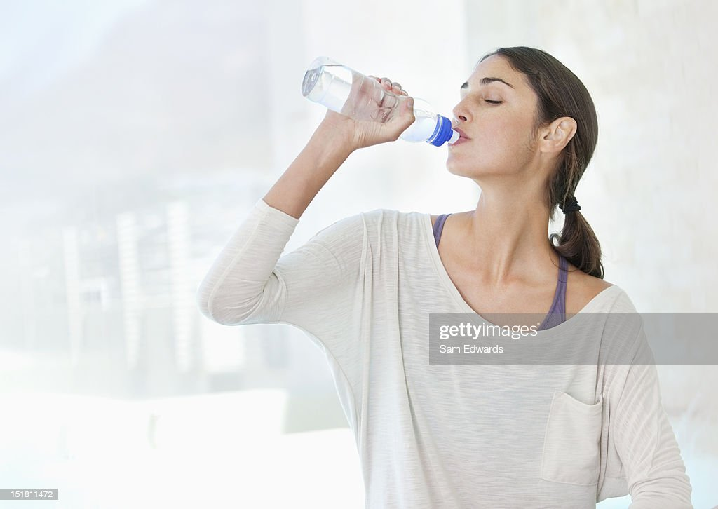 Woman drinking from water bottle : Stock Photo