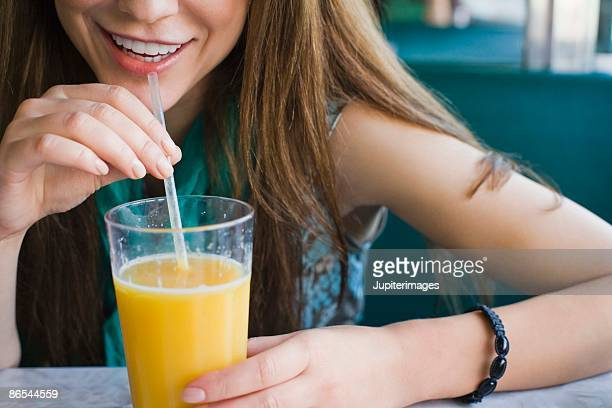 Woman drinking glass of orange juice with straw in diner