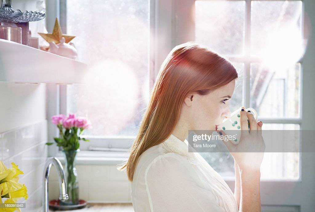 woman drinking hot coffee in kitchen in morning