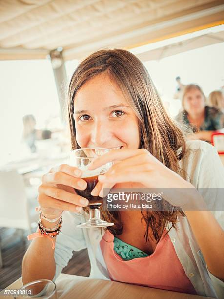 Woman drinking iced coffee at the beach bar