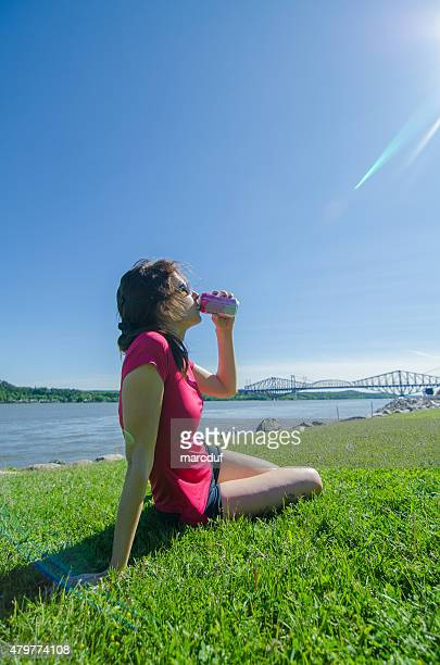 Woman drinking juice while sitting on grass
