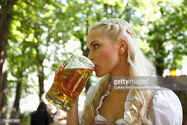 Woman drinking mug of beer outdoors