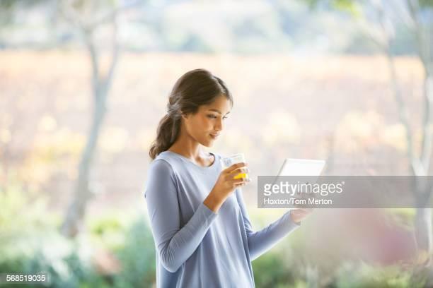 Woman drinking orange juice and using digital tablet